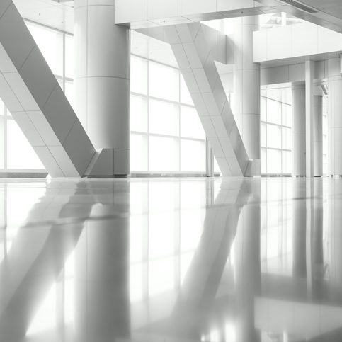 Light shining through the windows and columns of a modern architecture, with reflections on the floor.